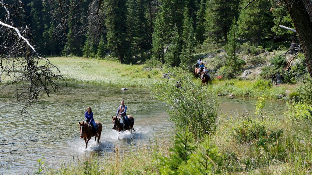 Horse riding treks through the ranch at Flat Creek Ranch in Wyoming as advertised by Kiwano Hotels